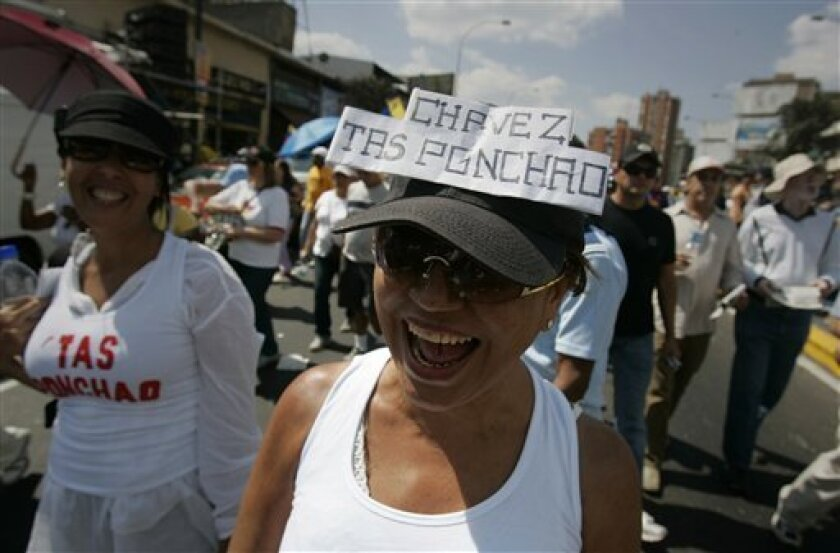 """In this photo taken Jan. 23, 2010, an opposition protester wears a cap that reads in Spanish """"Chavez you're struck out"""" in Caracas, Venezuela. The new slogan appearing on the T-shirts and banners of anti-government protesters in Venezuela sums up a growing sentiment about President Hugo Chavez after 11 years in power. (AP Photo/Leonardo Ramirez)"""