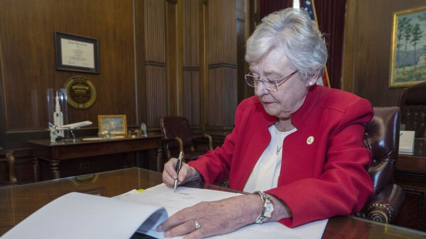 Alabama Gov. Kay Ivey signs a bill that virtually outlaws abortion in the state.