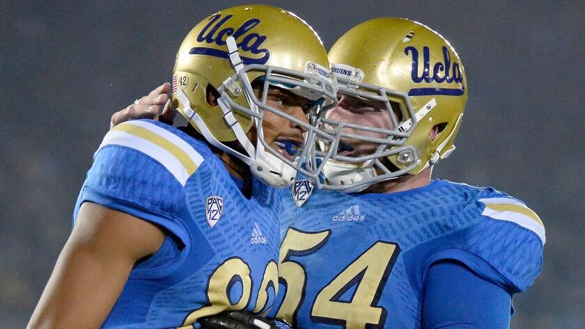 UCLA wide receiver Eldridge Massington, left, celebrates with center Jake Brendel after scoring a touchdown against USC on Saturday.