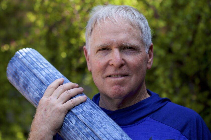 Dr. Ken Druck with a yoga mat.
