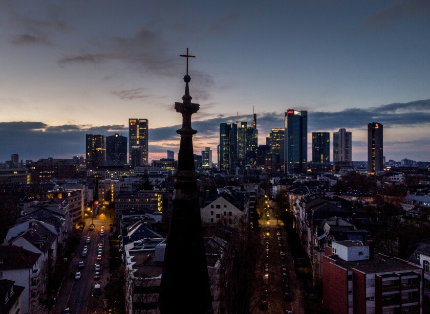 The buildings of the banking district stand behind a cross on top of a church in Frankfurt, Germany, on Good Friday, April 2, 2021. For a second year running the COVID-19 pandemic had a major effect on global celebrations of the Easter Holy Week. Many services were held outdoors or behind closed doors, but despite these restrictions the faithful found ways to mark one of the most important times in the Christian calendar. (AP Photo/Michael Probst)