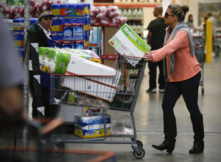 Suzanna Mitchell's shopping cart is filled with oversized packages, a key marketing feature at Costco.
