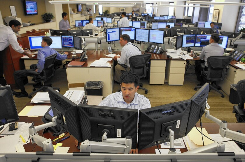 Patrick Ahn works on the trading floor at TCW Inc.'s office in Los Angeles. On Monday, traders with the company monitored news reports, looking for any scrap of intelligence from Greece or other global markets.