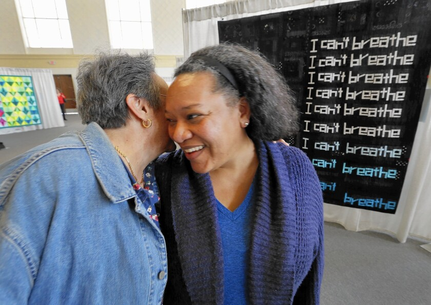 Chawne Kimber, right, whose quilt about Eric Garner won first in improvisational piecing at QuiltCon West, is congratulated by Joan D'Angostino.