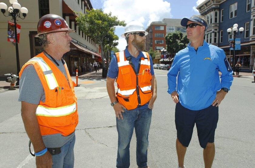 San Diego Chargers coach Mike McCoy talks with Joe McNulty, left, and Brian Kopp in the Gaslamp Quarters during the Chargers' Thank You San Diego Day where players and coaches fanned out across the city to interact with fans.