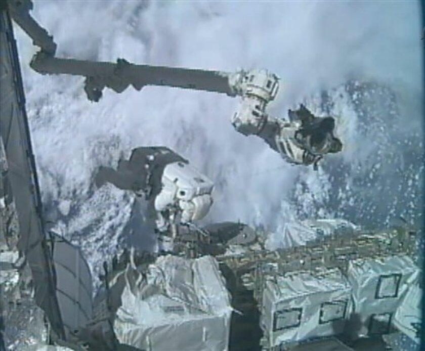 In an image made from video, astronaut Ronald Garan Jr. dangles outside the International Space Station during the last spacewalk of NASA's space shuttle era, with fellow astronaut Michael Fossum (not shown), Tuesday, July 12, 2011. They will retrieve a broken ammonia pump outside the International Space Station and pack it aboard the docked shuttle Atlantis. The two will also set up a robotic refueling experiment. (AP Photo/NASA)
