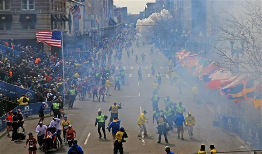 People react as an explosion goes off near the finish line of the 2013 Boston Marathon in Boston, Monday, April 15, 2013. Two explosions went off at the Boston Marathon finish line on Monday, sending authorities out on the course to carry off the injured while the stragglers were rerouted away from