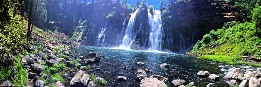 Burney Falls spills into a pool of water with large rocks and plants.