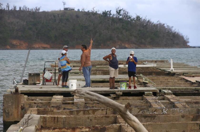 Fotografía de unos pescadores conversando sobre un dique destrozado por el paso del huracán María en el puerto de Humaco(Puerto Rico). EFE/Archivo