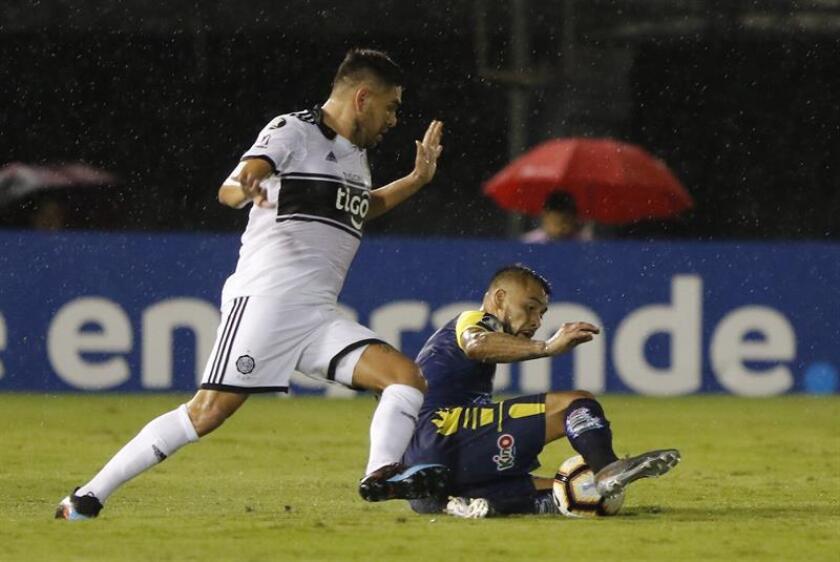 El jugador de Olimpia Jorge Ortega (i) disputa el balón con Guillermo Pacheco (d) de Universidad de Concepción este martes, durante el partido de la Copa Libertadores disputado en el estadio Defensores Del Chaco, en Asunción (Paraguay). EFE