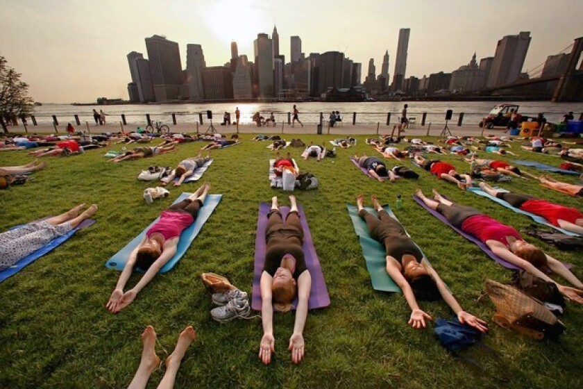 Touring the sights of New York can include fitness classes, such as this one in Brooklyn Bridge Park, across from lower Manhattan.