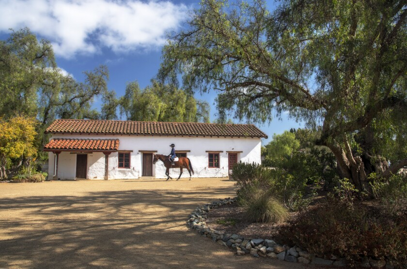 A rider on horseback passes the Juan Maria Osuna Ranch, one of the oldest adobe homes built in San Diego County.