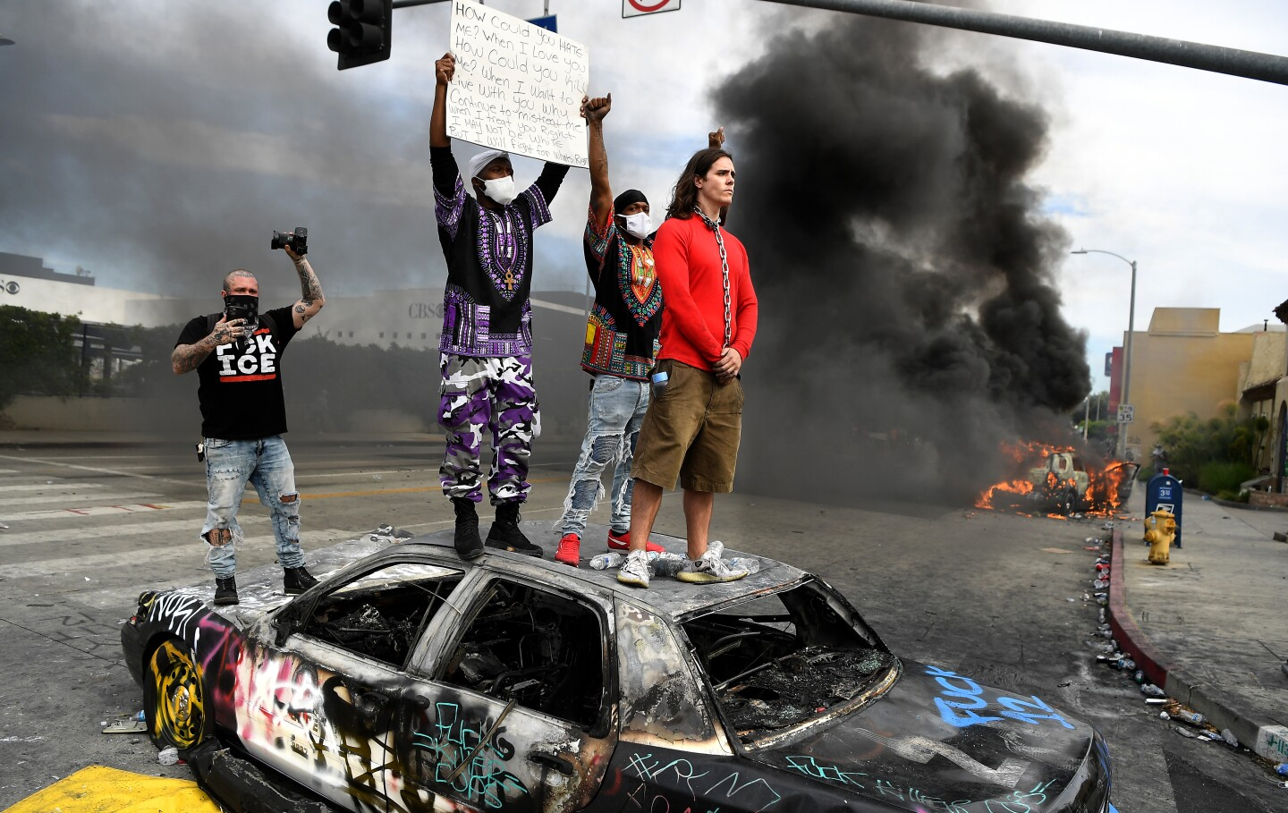 Protestors stand on top of a burned LAPD cruiser as another burns at 3rd Street and Fairfax Avenue in Los Angeles on Saturday.