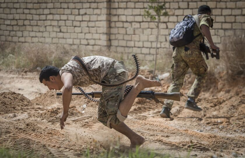 Fighters loyal to the Government of National Accord run for cover during clashes with forces loyal to strongman Khalifa Haftar south of Libya's capital, Tripoli, in April.