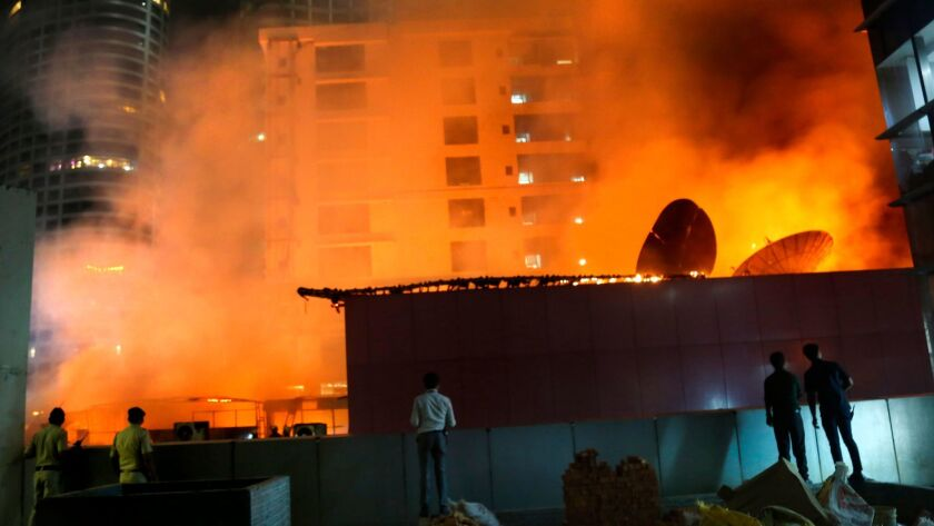 People watch as a huge fire engulfs a rooftop restaurant in Mumbai on Dec. 29.