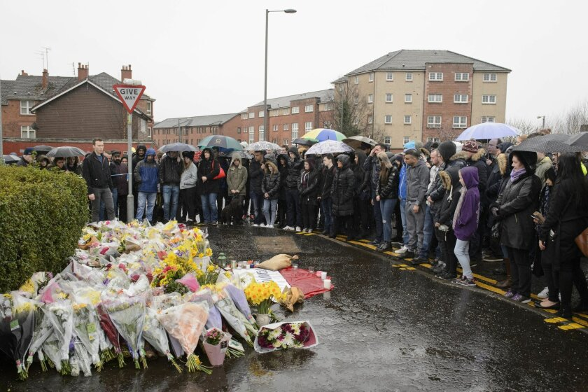 """A vigil is held outside the shop where Asad Shah worked in Glasgow, Saturday March 26, 2016. Scottish police say the killing of a Muslim shopkeeper who wished Christians a happy Easter is being investigated as """"religiously prejudiced."""" Vigils were held Friday and Saturday in memory of 40-year-old Asad Shah, who was killed Thursday night in Glasgow. (John Linton/PA via AP) UNITED KINGDOM OUT"""