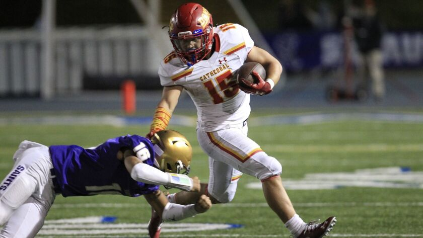 Cathedral Catholic running back Shawn Poma fends off St. Augustine tackler Jalil Tucker in the Dons' 34-14 win over the Saints on Friday night.