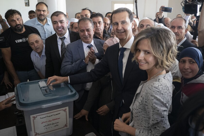 A grinning Bashar Assad casts his ballot surrounded by a crowd and his wife, Asma.