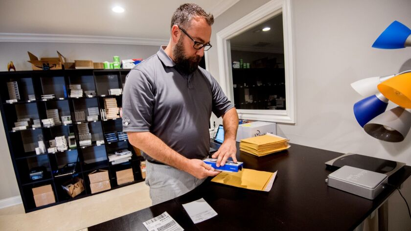 Dan Simpson packs an item for shipping at Fuse Chicken in Cuyahoga Falls, Ohio, in June.
