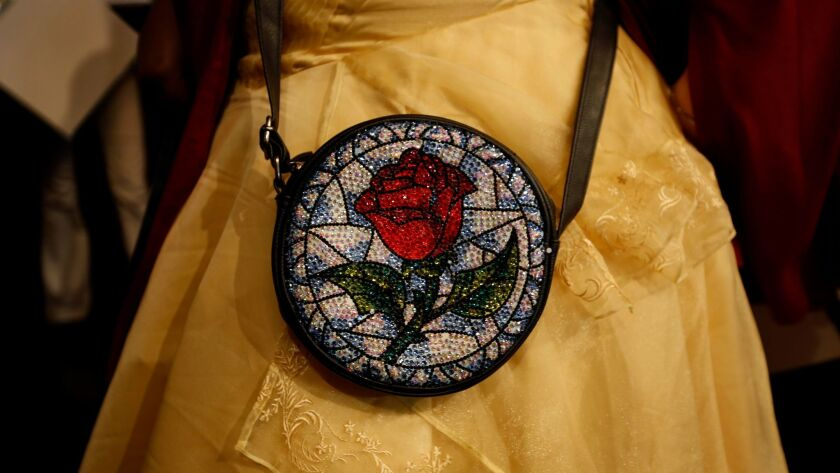 """Jennifer Miyano, 32, of Hermosa Beach shows the rose purse she decorated in honor of """"Beauty and the Beast,"""" which had its first L.A. public screening Thursday at Hollywood's El Capitan Theatre."""