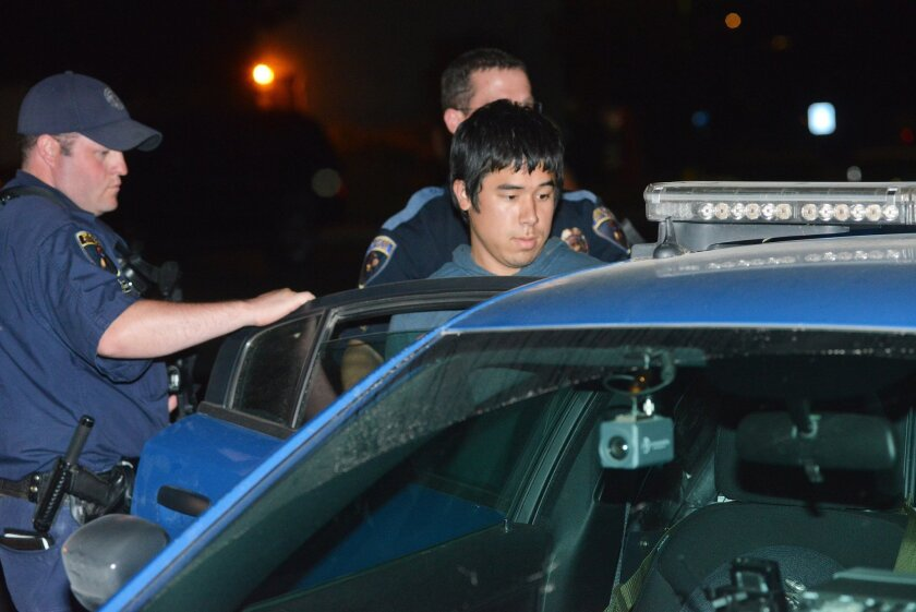 FILE - This Aug. 28, 2013 file photo shows Lukah Pobzeb Chang being put into of a patrol car by Pendleton Police after being arrested hiding at the convention center in Pendleton, Ore. The Marine Corps deserter pleaded guilty Wednesday, Jan. 8, 2014 to murdering a motel maid in 2012 and trying to beat to death a woman on a jogging path in 2013. He was sentenced to serve at least 35 years in prison. (AP Photo/East Oregonian, E.J. Harris, file)