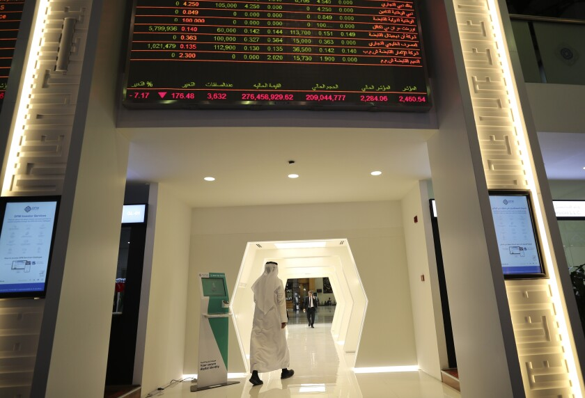 An Emirati trader passes under the stocks display screen at the Dubai Financial Market in Dubai, United Arab Emirates, Sunday, March 8, 2020. Stocks markets in the Mideast suffered sharp drops in early trading Sunday over fears about the new coronavirus and demand in crude oil falling amid a failure by OPEC and allied nations to cut production. (AP Photo/Kamran Jebreili)