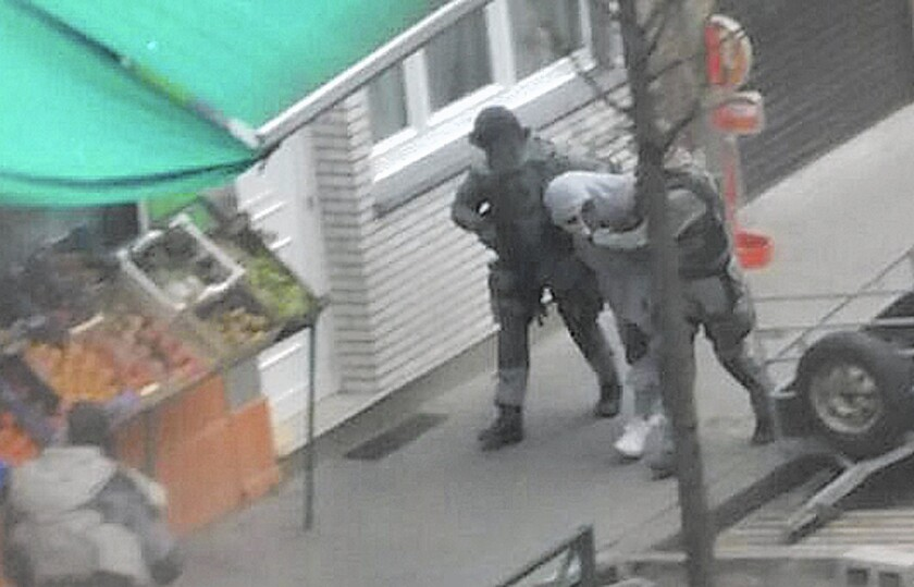 Police detain a man in Brussels' Molenbeek district on March 19 who is believed to be connected to a suspect in the Paris attacks. Residents say the district shouldn't be demonized for the actions of a few.