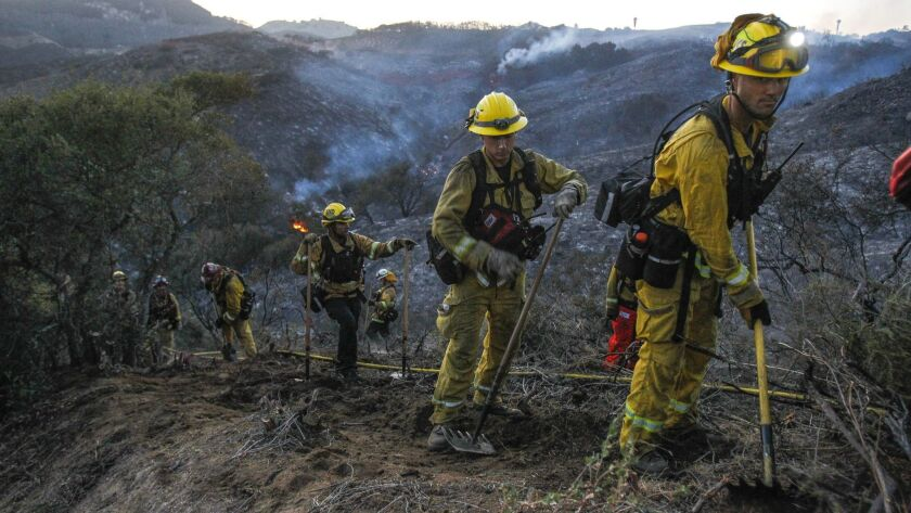 A hand crew of firefighters from various San Diego County fire departments scratch out a fire line after a brush fire burned in De Luz on Saturday.