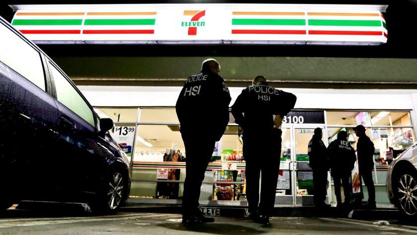 U.S. Immigration and Customs Enforcement agents serve an employment audit notice at a 7-Eleven conve