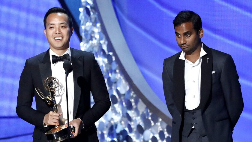 Alan Yang, left, accepts the Emmy for comedy writing with Aziz Ansari.