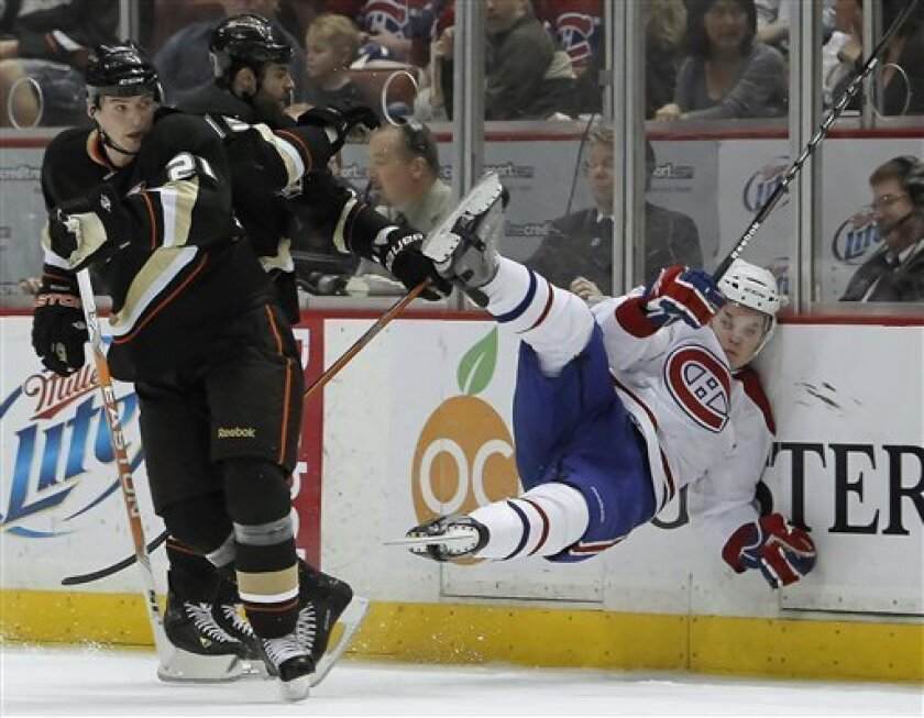 Montreal Canadiens center Ben Maxwell gets hit against the boards by Anaheim Ducks right wing Mike Brown as Sheldon Brookbank, left, looks for the puck in the first period during an NHL hockey game, Sunday, March 7, 2010, in Anaheim, Calif. (AP Photo/Alex Gallardo)