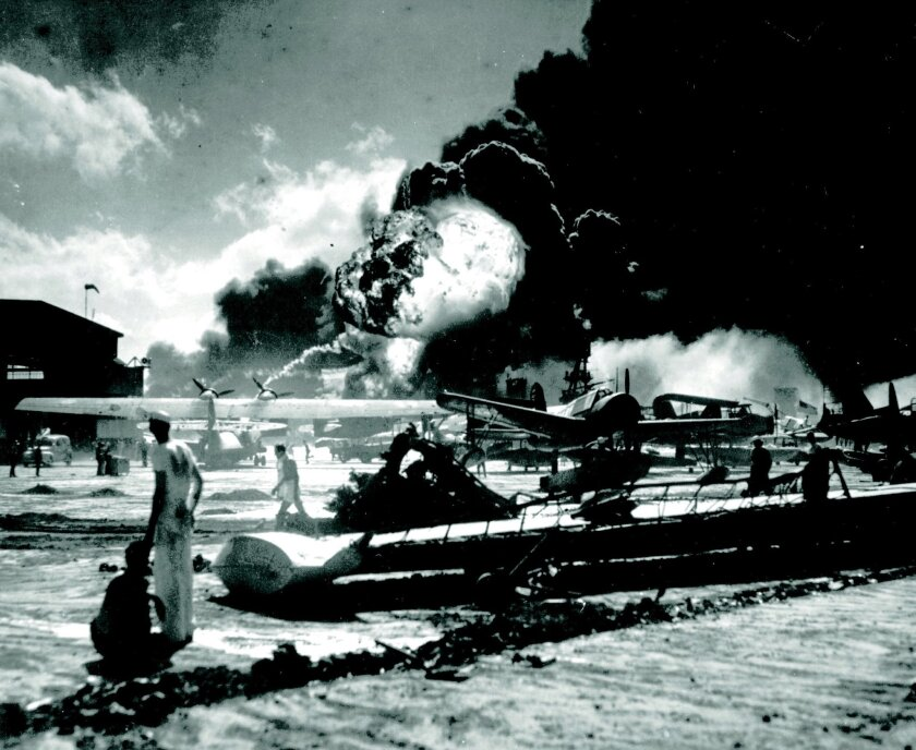 In this photo from U.S. Navy archives, sailors stand among wrecked airplanes at Ford Island Naval Air Station as they watch the explosion of the USS Shaw in the background during the Japanese surprise attack on Pearl Harbor, Hawaii, on Dec. 7, 1941. The attack led to the U.S. entry into World War