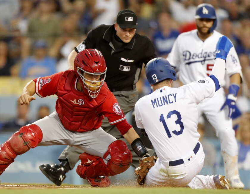 Angels catcher Dustin Garneau puts the tag on Dodges second baseman Max Muncy in the second inning July 23  at Dodger Stadium.