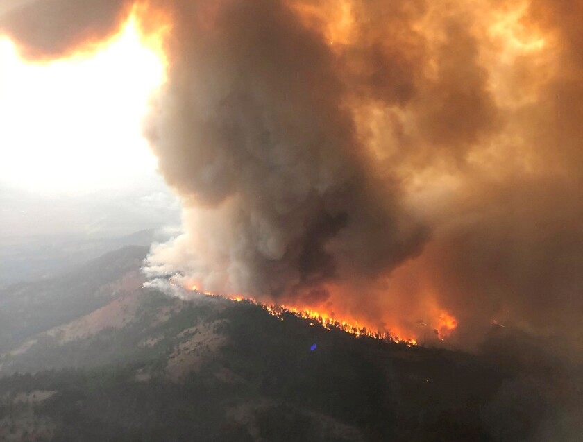 An aerial photo shows a huge plume of smoke on a ridge as the Dixie fire burns.