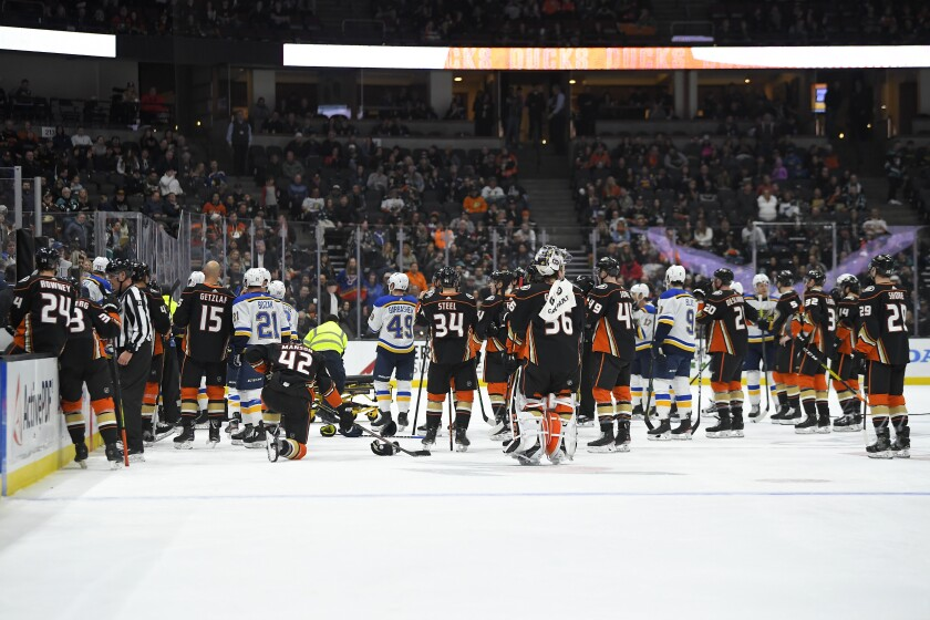 Ducks and Blues players gather on the ice after Jay Bouwmeester went into cardiac arrest while on the bench.