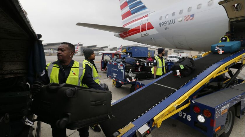 Workers unload bags from an American Airlines flight at Los Angeles International Airport. The average domestic airfare dropped to its lowest inflation-adjusted level since at least 1995.