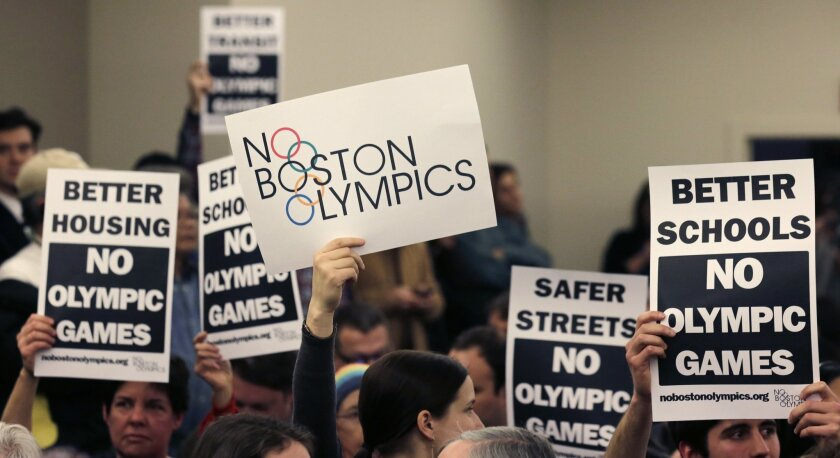"FILE - In this Feb. 5, 2015, file photo, people hold up placards against the Olympic Games coming to Boston, during the first public forum regarding the city's 2024 Olympic bid, in Boston. Boston's mayor delivered a harsh blow to the city's effort to host the 2024 Olympics on Monday, July 27, 2015, when he declared he wouldn't sign any document ""that puts one dollar of taxpayer money on the line for one penny of overruns on the Olympics."" That document is the host city contract that most in the Olympics consider crucial to any city's success. (AP Photo/Charles Krupa, File)"