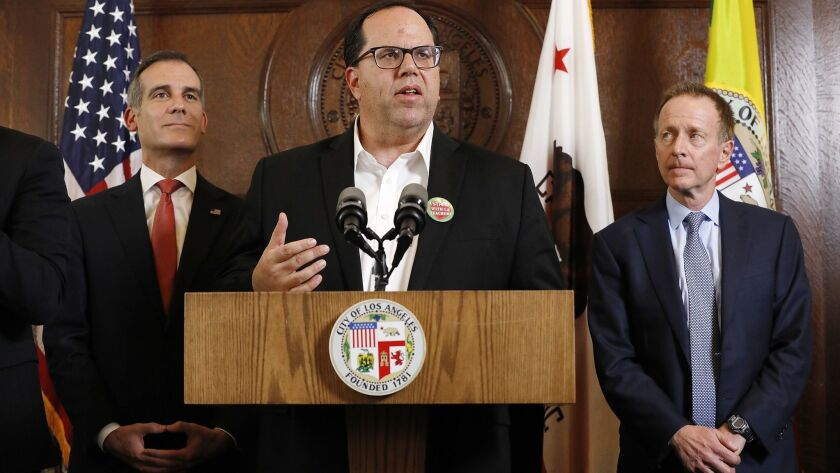 United Teachers Los Angeles President Alex Caputo-Pearl is flanked by L.A. Mayor Eric Garcetti, left, and LAUSD Supt. Austin Beutner while speaking about a resolution to the teachers' strike Tuesday.