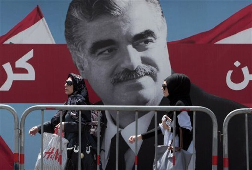 Lebanese women pass by a giant portrait of slain Lebanese Prime Minister Rafik Hariri near his grave, in downtown Beirut, Lebanon, on Thursday June 30, 2011. A U.N.-backed court investigating the 2005 assassination of former Prime Minister Rafik Hariri delivered an indictment and four arrest warrants Thursday, the latest turn in a case that has transformed the Arab nation and brought down the government earlier this year. The names of the accused were not released, but the court has been expected to accuse members of the Iran-backed militant group Hezbollah. (AP Photo/Hussein Malla)