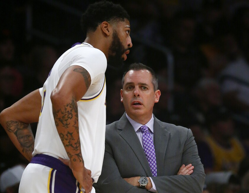 Lakers forward Anthony Davis chats with coach Frank Vogel during a game this season.