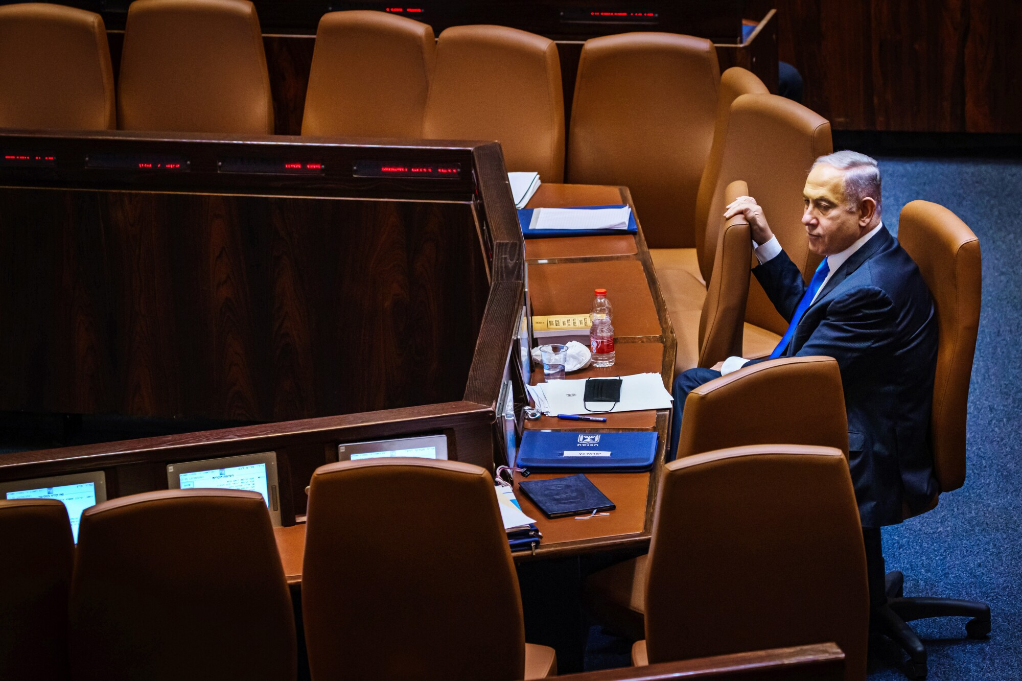 Outgoing Prime Minister Benjamin Netanyahu takes a look around the empty seats as members of the Knesset.