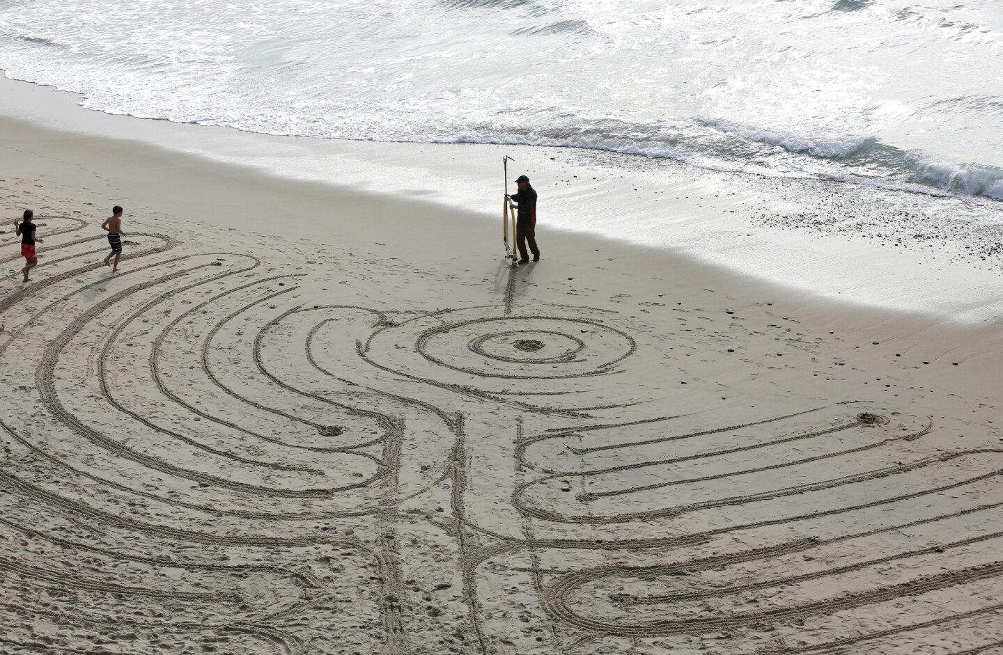 Encinitas artist Kirkos creates a huge labyrinth on the beach at Grandview Beach in Encinitas to ring in the new year.