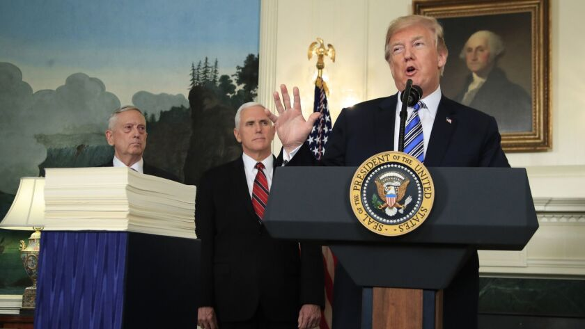 President Trump, with Defense Secretary James N. Mattis, left, and Vice President Mike Pence, announces in March his signing of a $1.3-trillion spending bill.