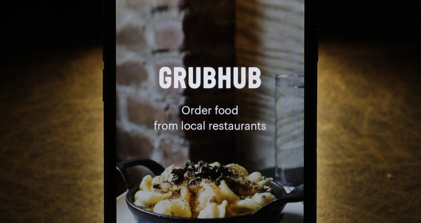 FILE - This Feb. 20, 2018, file photo shows the Grubhub app on an iPhone in Chicago. Food delivery service Grubhub is considering a possible sale of the business as competition intensifies in the sector. The Wall Street Journal reports that the company is looking at its strategic options. Grubhub competes in a sector filled with players including Uber Eats, DoorDash and Postmates. Consolidation in the industry is expected. (AP Photo/Charles Rex Arbogast, File)