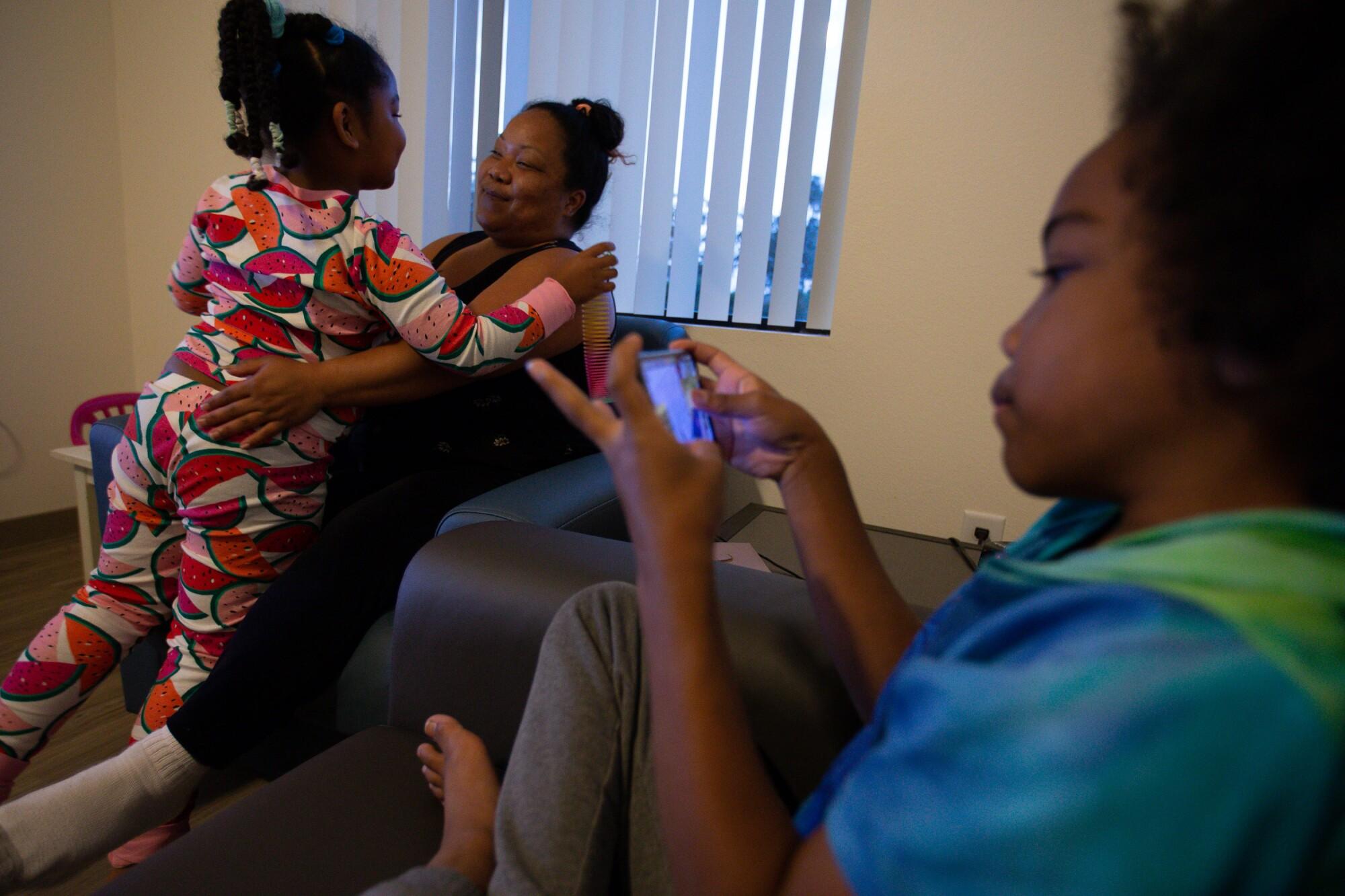 Janelle Miller embraces her daughter Anastazia alongside her son at the Salvation Army's Door of Hope transitional program