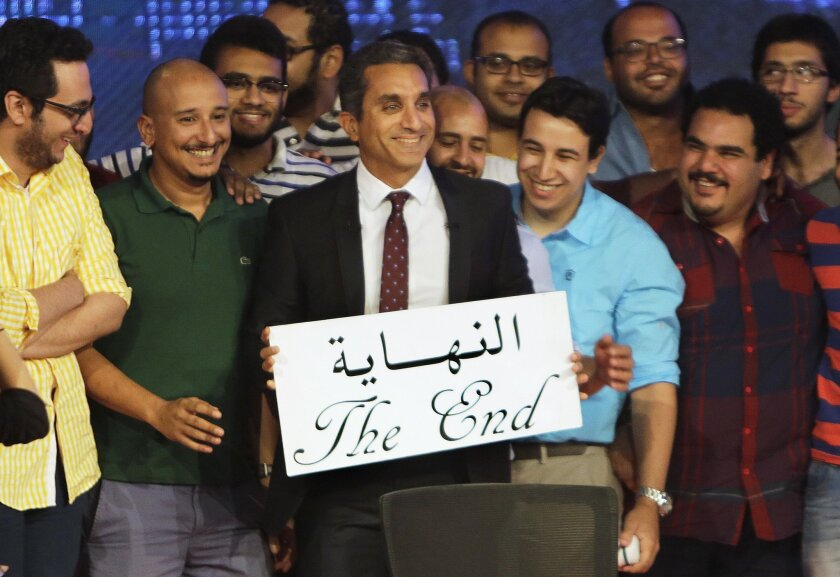 "Egyptian satirist Bassem Youssef, who is known as ""Egypt's Jon Stewart,"" poses with his team with an English and Arabic placard reading ""the end,"" during a press conference in Cairo, Egypt, Monday, June 2, 2014. Youssef said Monday he has canceled his landmark TV show, which broke ground by lambasting its politicians and elites and mocking the pro-military fervor of the past year. Youssef said the atmosphere in the country no longer allows for political satire. (AP Photo/Amr Nabil)"