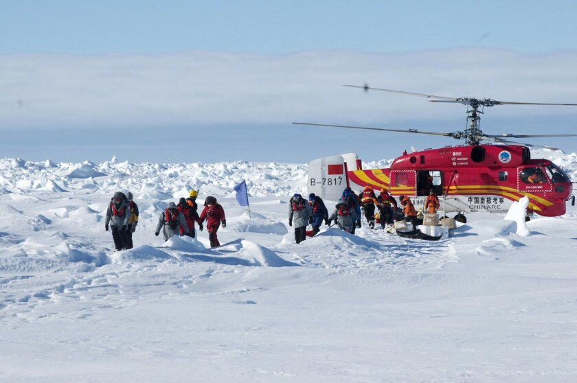 In this image provided by Australasian Antarctic Expedition, passengers trapped for more than a week on the icebound Russian research ship MV Akademik Shokalskiyin are rescued by a Chinese helicopter Thursday, Jan. 2, 2014.  The helicopter rescued all 52 passengers from the research ship that has b