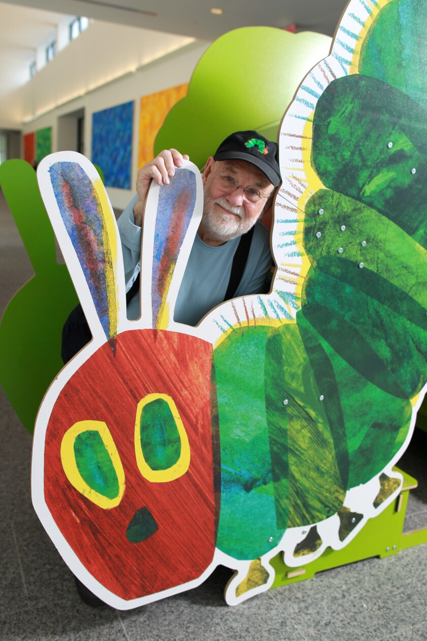 """Eric Carle stands with large cutout of the iconic image from his children's book, """"The Very Hungry Caterpillar"""""""