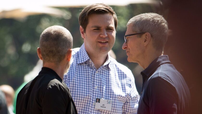Venture capitalist and author J.D. Vance, center, shakes hands with Tim Cook, right, chief executive officer of Apple, at the Allen & Co. Sun Valley Conference in 2017.