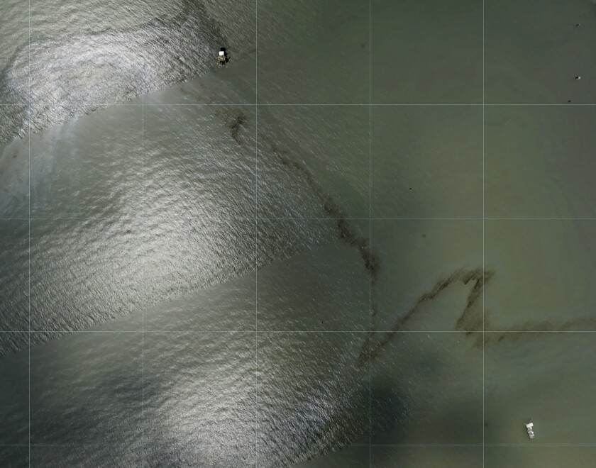 Overhead view of a miles long black slick floating in the Gulf of Mexico near a large rig.